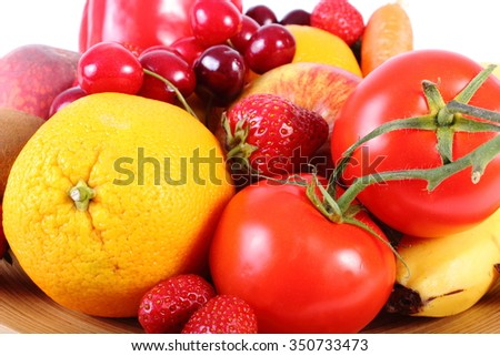 Fresh ripe fruits and vegetables lying on wooden plate, concept of healthy food, nutrition and strengthening immunity. Isolated on white background