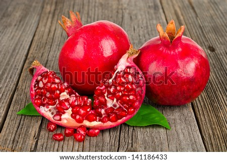 Fresh ripe pomegranates with leaves on an old wooden board