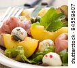 Fresh salad with peach, mozzarella cheese and ham. Selective focus - stock photo