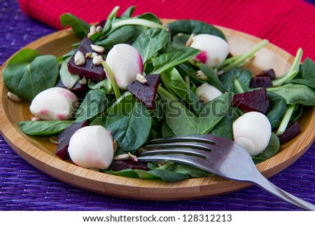 Fresh salad with roasted beets, spinach, mozzarella and seeds