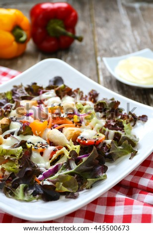 Fresh salad with tomato,cucumbers,Lettuce,corn,Purple lettuce with salad dressing Red tablecloth