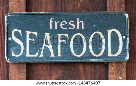Fresh Seafood restaurant sign on wooden wall