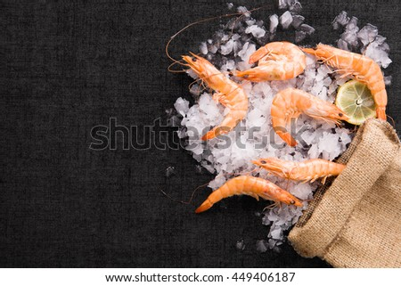 Fresh shrimp with lemon on ice in brown burlap bag on black table, top view. Culinary seafood eating.