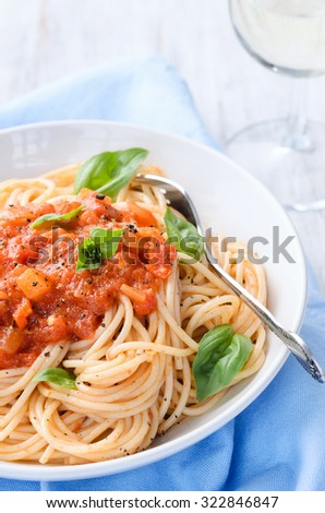 Fresh spaghetti pasta with tomato sauce basil leaves and glass of white wine
