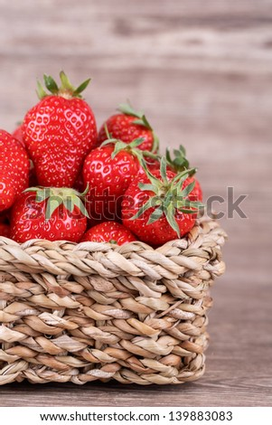 fresh strawberries in a basket on a wooden background