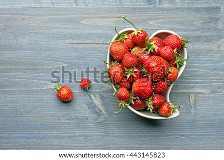 Fresh strawberries in a plate in the shape of a heart on wooden table