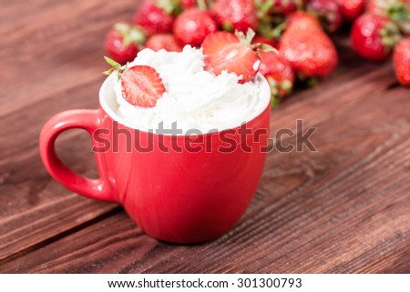 Fresh strawberries with cup of cream on old wooden background
