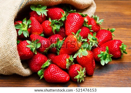 fresh strawberry in burlap sack on wood