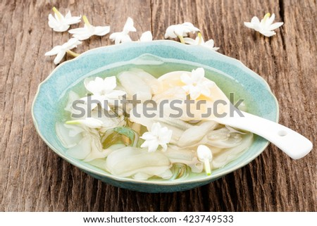 Fresh toddy palm fruit and bowl of Thai dessert on wood background, with a smell of jasmine, Thailand vintage style