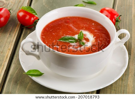 Fresh tomato soup in a white bowl on a wooden table