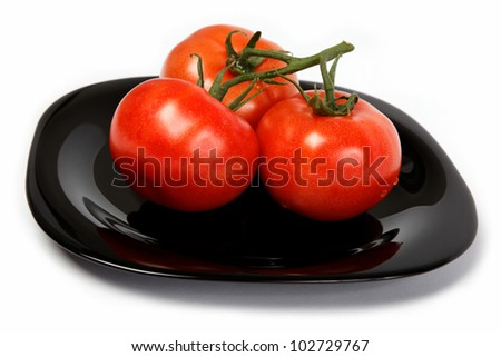 Fresh tomatoes on a plate, isolated on a white background.