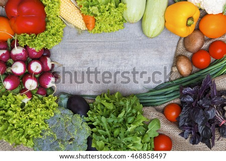 Fresh vegetables on wood background with free space for text