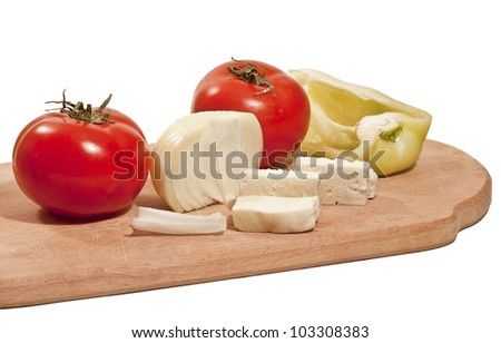 Fresh vegetables with cheese on the chopping board isolated on white background
