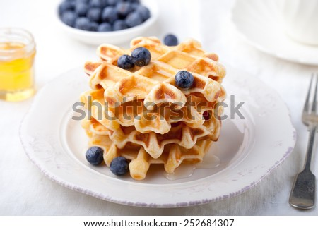 Fresh waffles with blueberries and pouring honey, maple syrup on a white background. Breakfast table