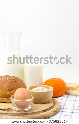 Fresh whole grain bread, milk, egg, orange and wheat.
