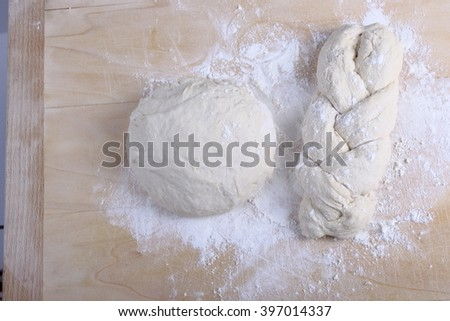 Fresh yeast dough on a wooden board with flour and dough cutter