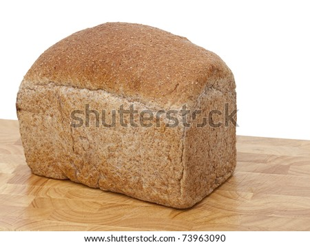 Freshly baked loaf of brown, wholemeal bread on a cutting board against a pure white background