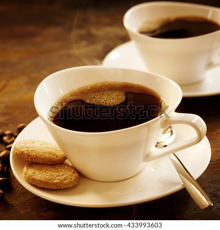 Freshly brewed cup of strong espresso coffee with cookies served in a stylish modern white cup and saucer with a second cup behind in square format