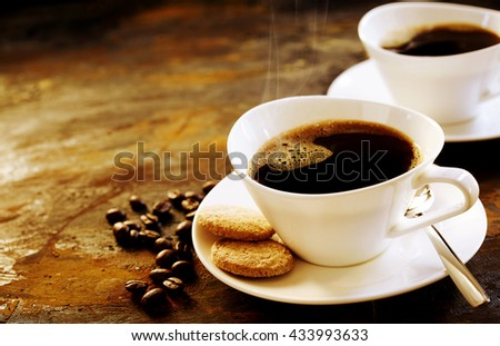 Freshly brewed espresso coffee served in a stylish modern cup with two cookies on a wooden table with scattered coffee beans and copy space