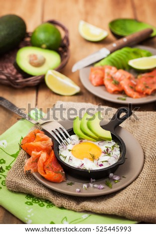 Fried egg, avocado and smoked salmon in frying pan served for breakfast