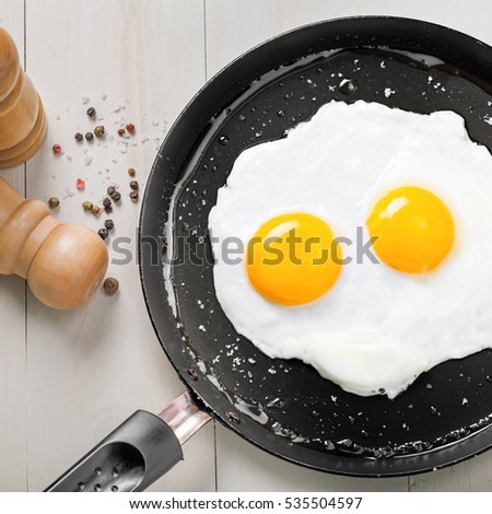 Fried eggs for delicious healthy easy breakfast on a table. Fresh homemade meal on a frying pan. Traditional breakfast food. International cuisine food.  Top view.