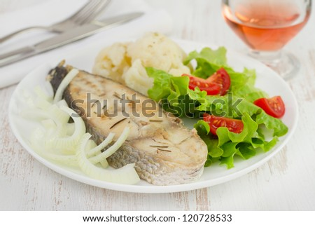 fried fish with cauliflower and salad on the white plate