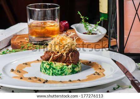 Fried meat with whiskey sauce and potato puree with spinach