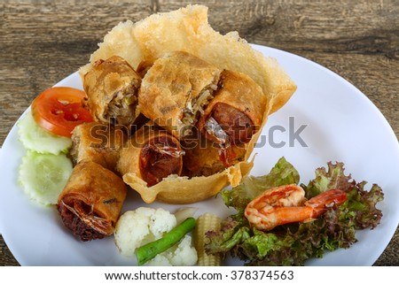 Fried spring rolls in eatable basket with salad leaves