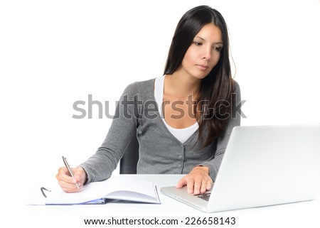 Friendly attractive young woman working at a desk with her laptop computer writing notes in a notebook conceptual of a hardworking office worker or businesswoman, or a student studying by e-learning