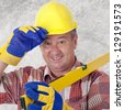 Friendly construction worker with a spirit level and safety gloves - stock photo