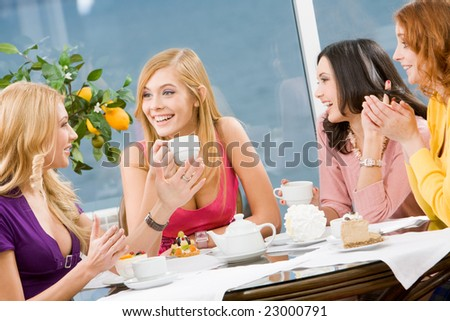 Friendly conversation of four pretty girls during lunch