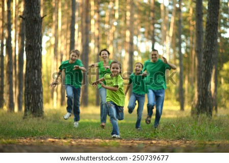 Friendly family running together in autumn park