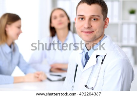 Friendly male doctor  on the background with patient  in hospital. High level and quality medical service concept.