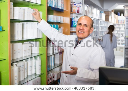 Friendly smiling male pharmacist at the work in drugstore
