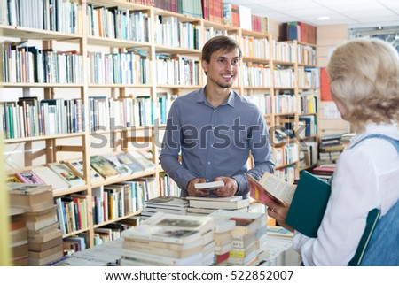friendly smiling young male seller consulting customer in book shop