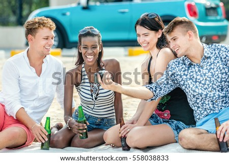 Friends having fun during vacation. Group of young cheerful people having fun while drinking beer on the beach together.