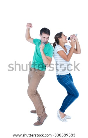 Friends singing in a microphone back to back on white background