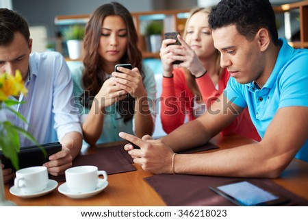 Friends using mobile phones at cafe