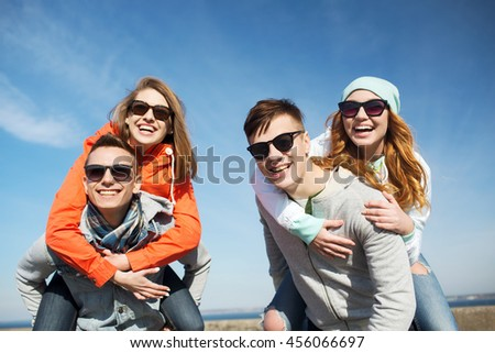 friendship, leisure and people concept - group of happy teenage friends in sunglasses having fun outdoors