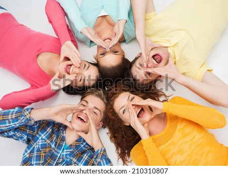 friendship, youth, gesture and people - group of smiling teenagers lying on floor in circle and shouting