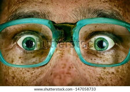 Frightened look of a man in old glasses close up
