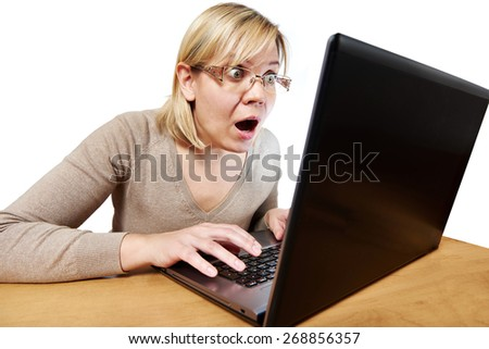 Frightened woman with glasses looking at a laptop isolated