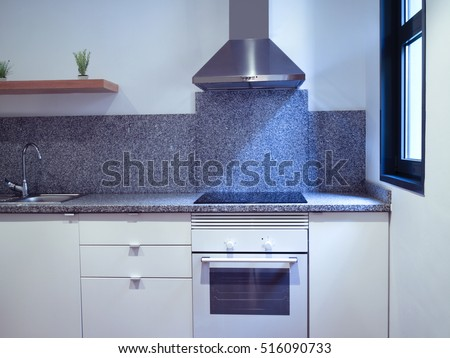 front of a small apartment kitchen with white furniture, oven, stainless steel cooker hood, grey granite splashback and worktop