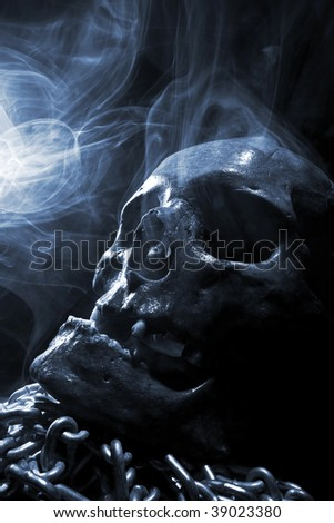 front of real skull with chain in abstract smoke