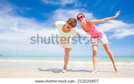front view of happy young couple waving hands at tropical beach