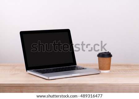 Front view of the laptop and take-out coffee  is on the work table concrete background