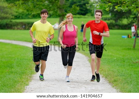 Front view of three athletes jogging in the park
