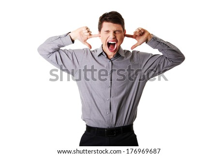 Front view portrait of a young angry man plugging his ears and shouting, on white.