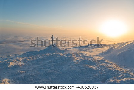 Frosted cross against beautiful sunrise scene in mountains. Human figure is seen in the middle distance.