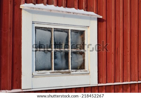 Frosty old window, white frames and red wall.